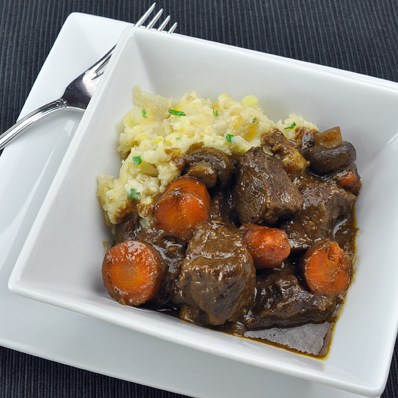 Guinness Beef Stew served atop Cauliflower Colcannon w/ Garlic Scapes. A meal fit for Saint Patrick himself.